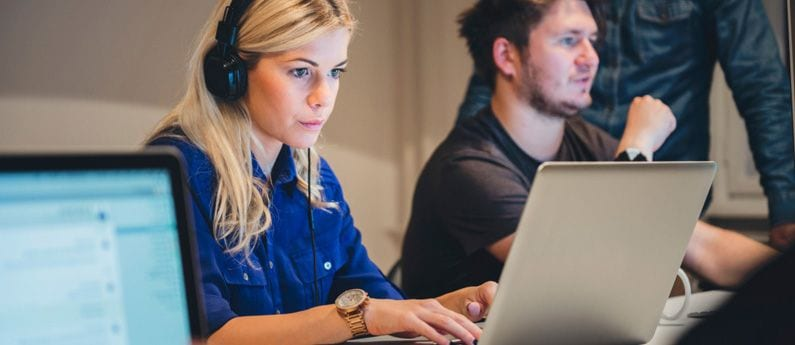 A young blonde woman wearing headphones and a large watch stares intently at a laptop computer screen while a couple of her colleagues chat in the background