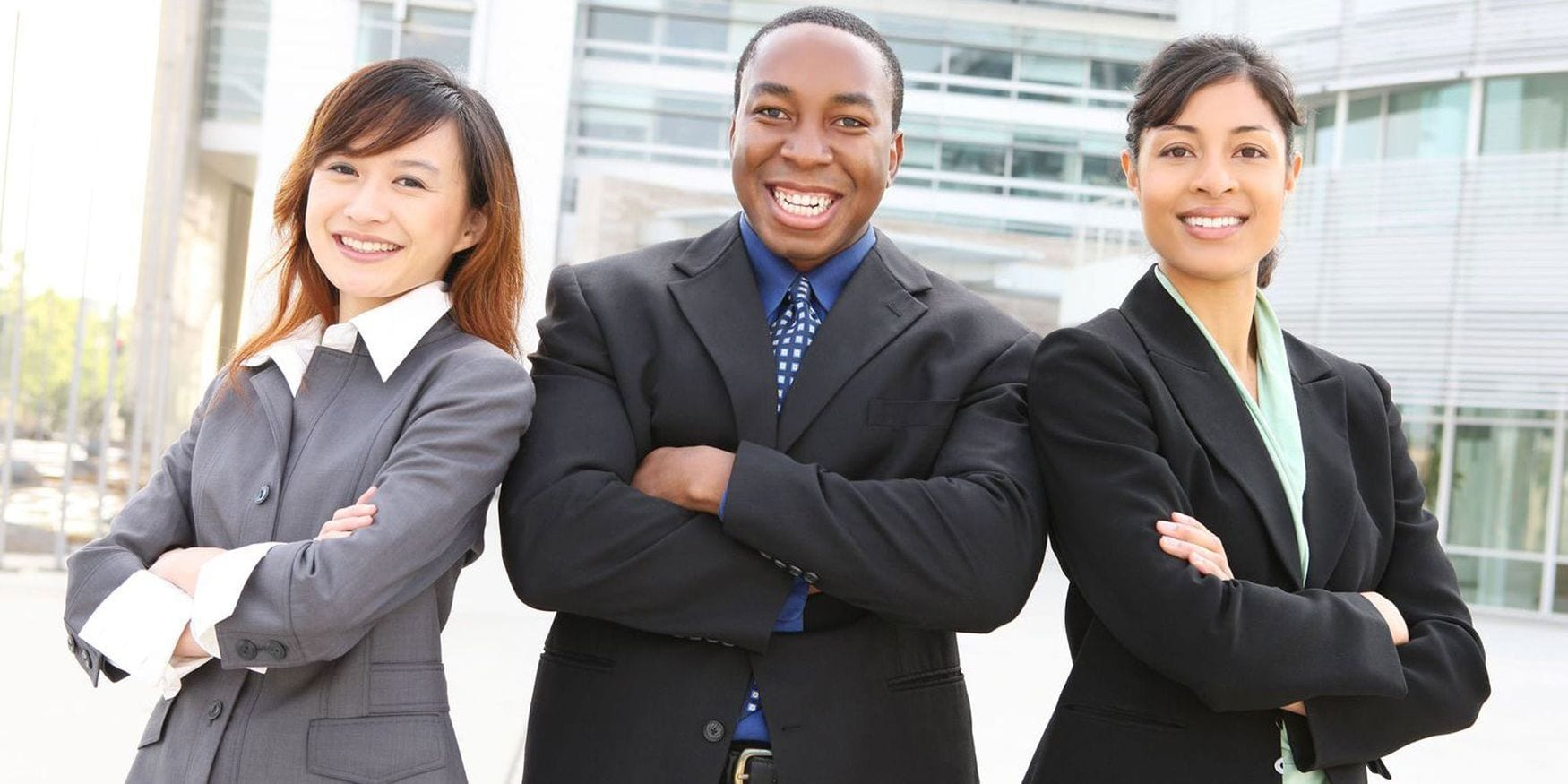 Two business women and one business man are standing with their arms crossed and smiling at the camera