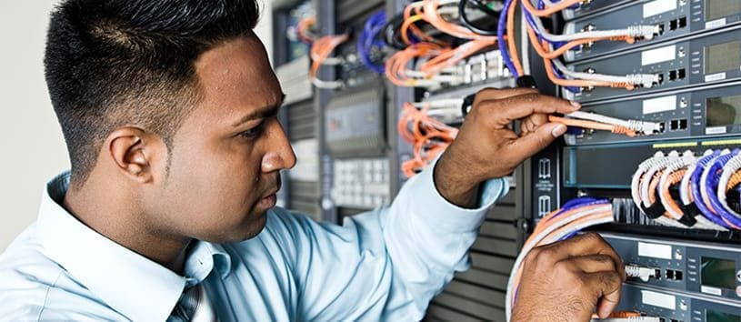 A close-up of a focused South-Asian man playing with cables on a network server