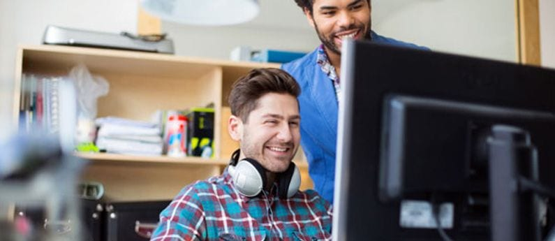 A pleasant and somewhat geeky-looking young man appear to be almost laughing while staring at a computer monitor, and a dapper colleague stands over his shoulder also looking at the monitor with a big smile.