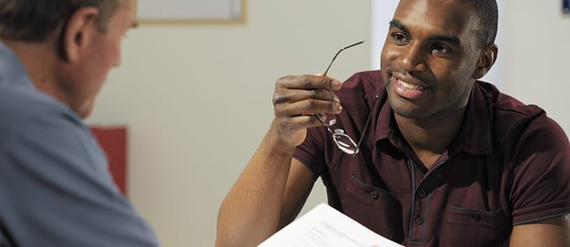 A handsome, Arican-American man with an athletic build is holding his glasses in his hand and smiling as he looks across from him at another clean-shaven man who is reviewing something on a piece of paper