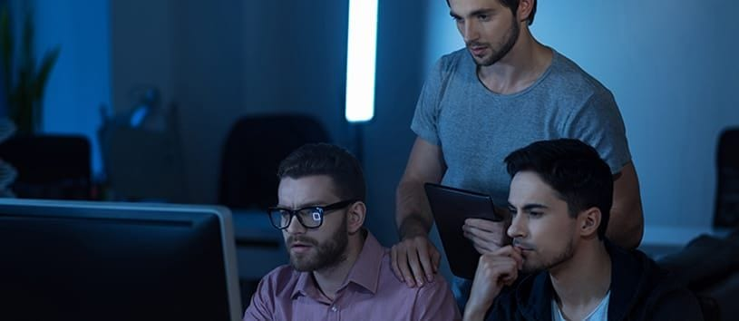 Three handsome men, two sitting and one standing, are looking at a computer screen in a dark room with perplexed looks on their faces