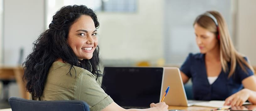 A woman with dark, wavy hair, a great smile, and dimples, is looking over her shoulder at you from the desk where she's working on a laptop