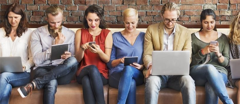 Six mainly caucasian people, two men and four women, all quite fashionably dressed, are sitting on a long couch and every one of them is looking at a screen—laptops, tablets, and phones